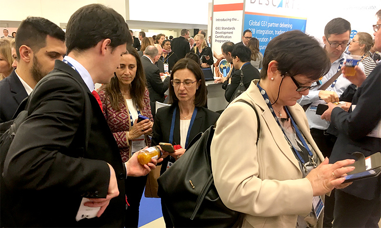 People at the GS1 Global Forum scanning products with the GS1 Hunt mobile apps.