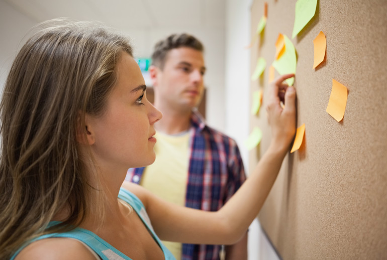 A product owner shows a stakeholder how a Scrum project will work via post-its on a board.