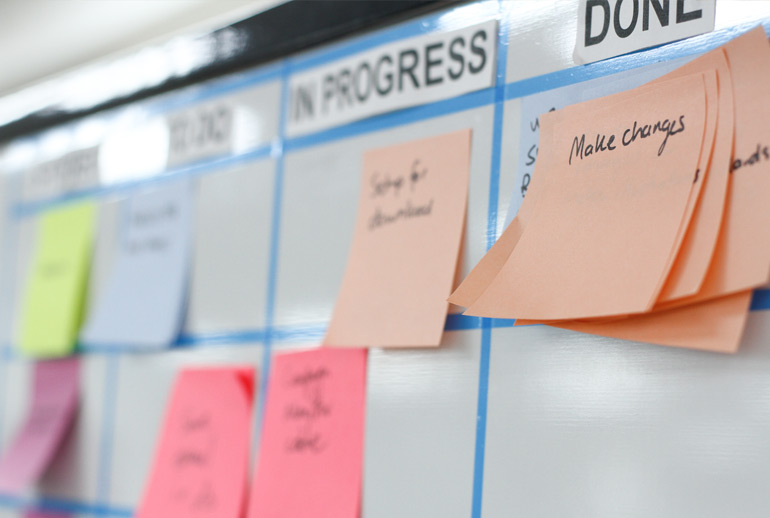 You can record the status of user stories in Scrum by moving the story along a physical board like this one using post-its on a whiteboard divided into columns showing status.