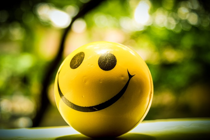 Smiley face ball against a leafy background. Photo by chaitanya pillala on Unsplash.