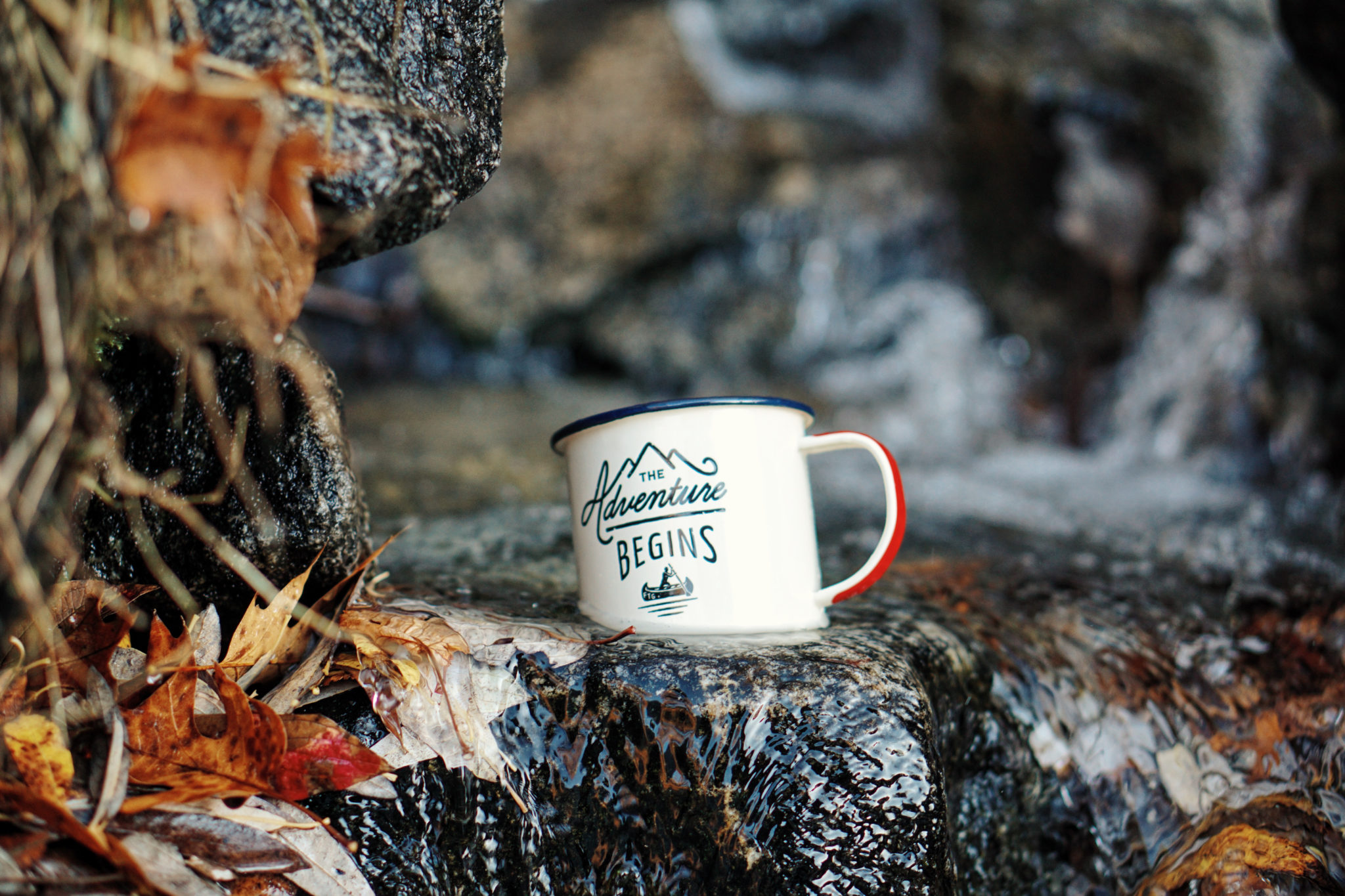 An enamel mug reading 'The adventure begins' sits in a stream. The Team Charter sets ground rules for the upcoming project.