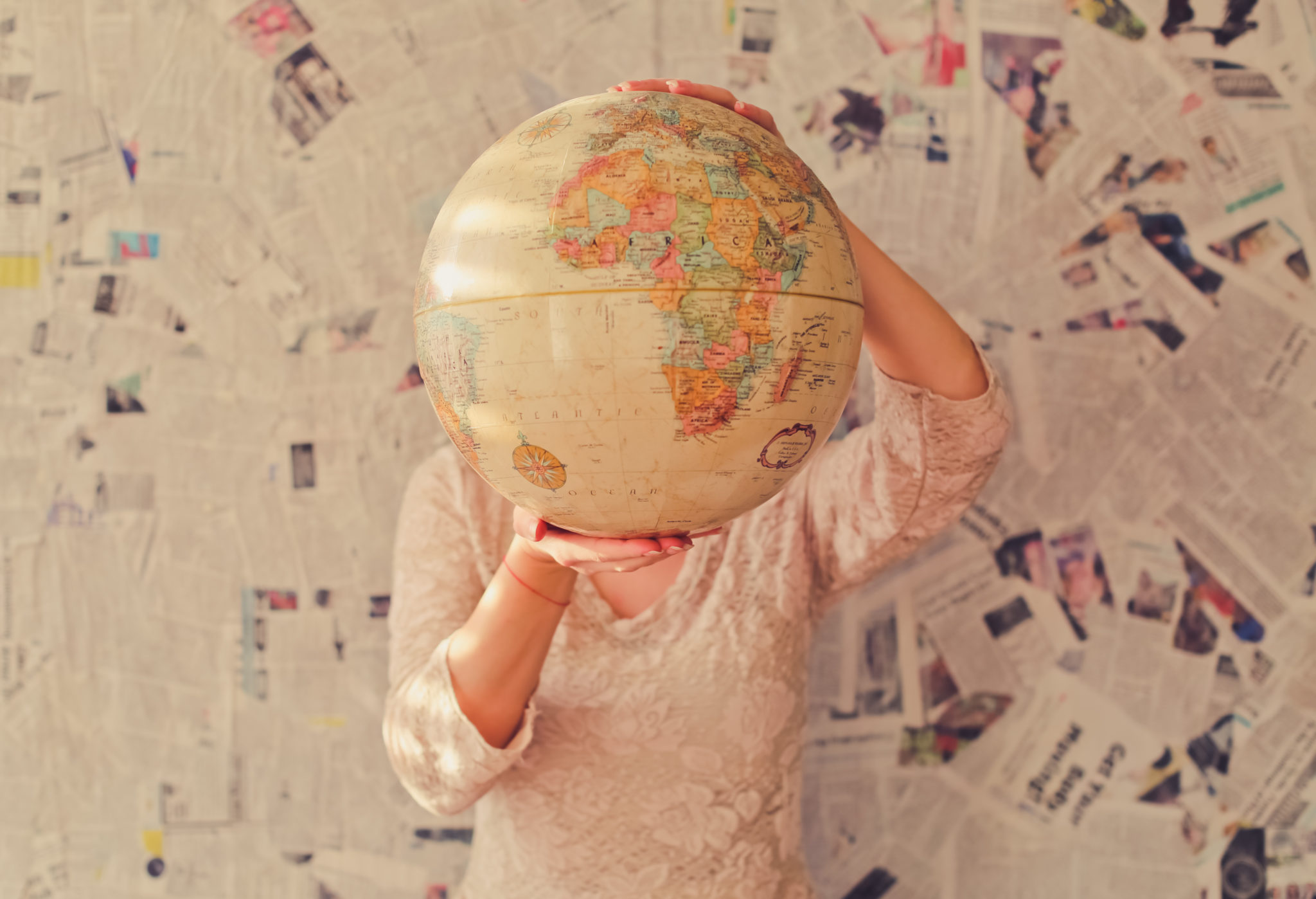 A woman holds up a globe. User story mapping guides you to your destination - building your product.