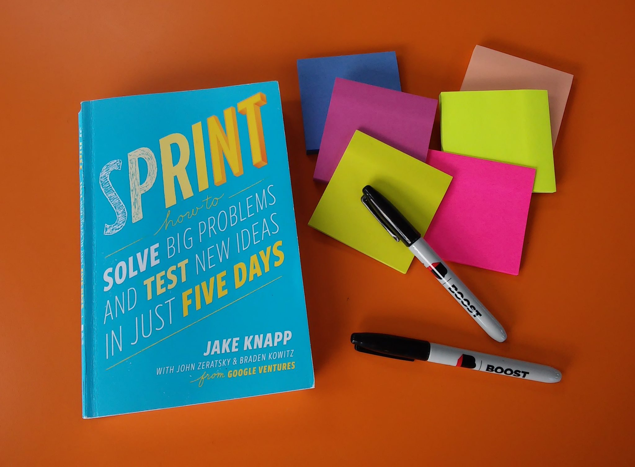 The Google Design Sprint book with post-its and pens.