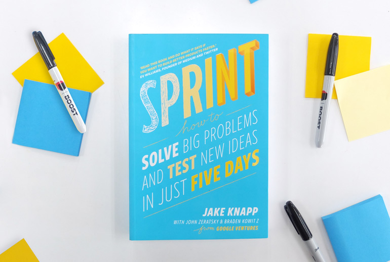Click the photo of the Sprint book on a desk with sharpies and post-its to view of Google Design Sprint guide.