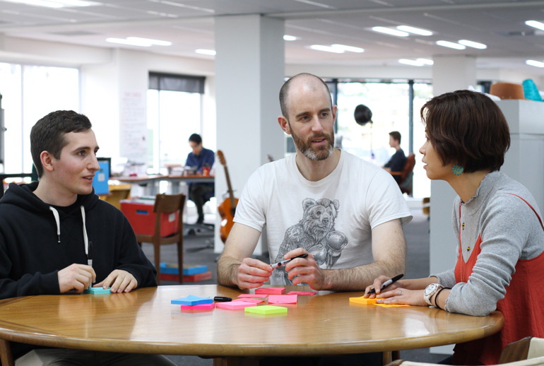 A team discuss user story tasks with post-its at a table. Conversation is one of the key features of user stories in Scrum.