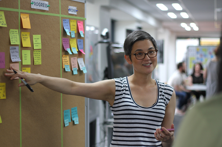 A Product Owner in front of a Scrum board. These boards are a key Agile transparency tool for reducing project risk.