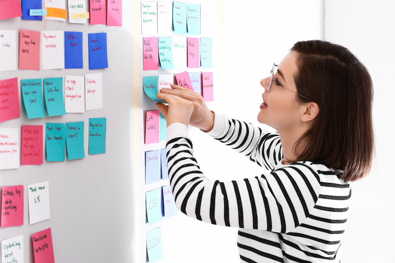 Product owner moves completed stories on a Scrum board, reducing WIP to limit risk.