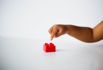 Child with one red lego block. Playing with Lego has revealed a new cognitive bias. Photo by @calebeangel via Unsplash.