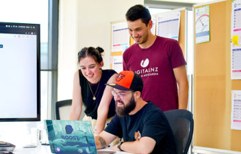 A Boost designer works with two colleagues. Tight-knit teams make these Wellington UX designer jobs special.