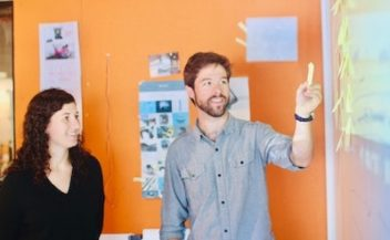 Team members at a whiteboard while taking part in an Individual strengths retrospective. Photo by Tool Inc on Unsplash.